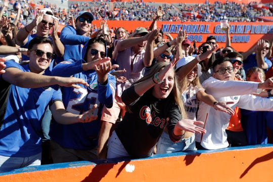 """Florida fans do the """"gator chomp"""" as they cheer Nov. 17, 2018, during the second half of the game against Idaho in Gainesville."""
