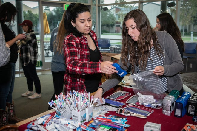 California Lutheran University students  Sofia Mikaeili and Olivia Kemp pack supplies for people displaced by the Woolsey and Hill fires that broke out on Nov. 8. Some of the people displaced by the fires took shelter at the university.