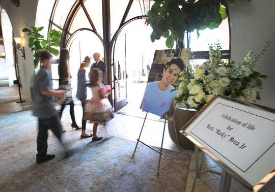 Mourners pass a photo of Mark Meza Jr. in the lobby of the Hilton Resort in Santa Barbara during Sunday's celebration of life ceremony honoring one of the victims of the Borderline Bar & Grill shooting.