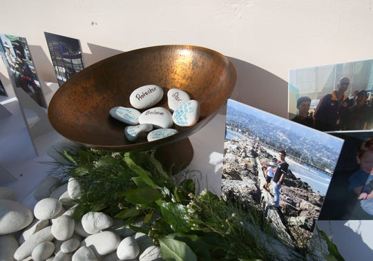 Mourners put their personal messages on rocks during a celebration of life ceremony honoring Mark Meza Jr., who was one of the 12 people who were killed at the Borderline Bar & Grill shooting in Thousand Oaks, at Hilton Resort in Santa Barbara on Sunday.