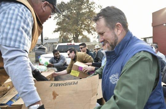 Visalia Breakfast Lions president Stephen Johnson helps deliver 100 turkeys to the Bethlehem Center Monday morning.