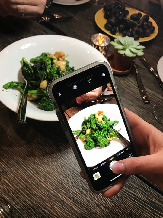 """Taking a photo of the """"Rabes,"""" sauteed broccoli rabe with oven roasted garlic and chili flake at Joe & Joe in Nyack. Photographed Nov.16, 2018."""