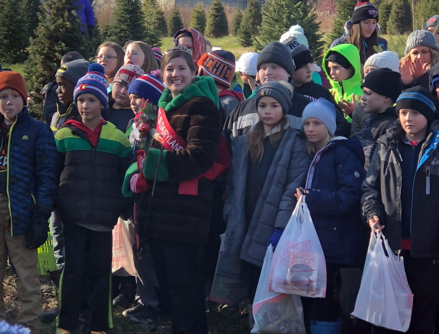 Surrounded by New Glarus and Albany fourth and fifth grade students, Alice in Dairyland, Kaitlyn Riley, gets ready to help cut a tree at Lancaster's Winterberry Tree Farm in Brooklyn to mark the 2018 Christmas tree season on Nov. 15.