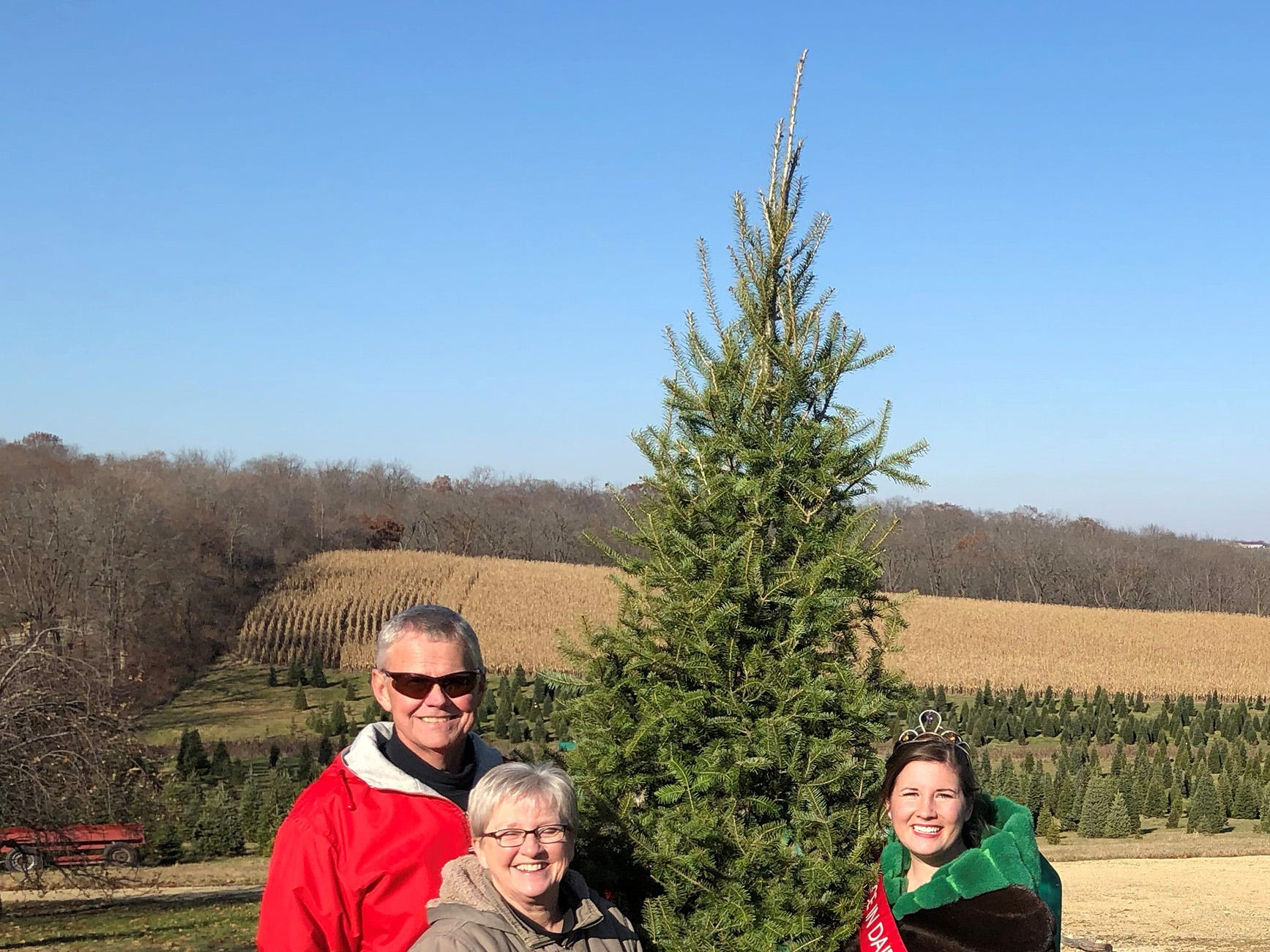 Alice in Dairyland Kaitlyn Riley (right) is pictured with owners of Winterberry Tree Farm Greg and Vickie Lancaster after Riley helped cut down a tree to mark the 2018 Christmas tree season.