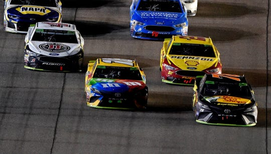 Martin Truex Jr. (78) pased Kyle Busch (18) on the final restart as Joey Logano (22) and Kevin Harvick close in during the Ford EcoBoost 400 at Homestead-Miami Speedway.