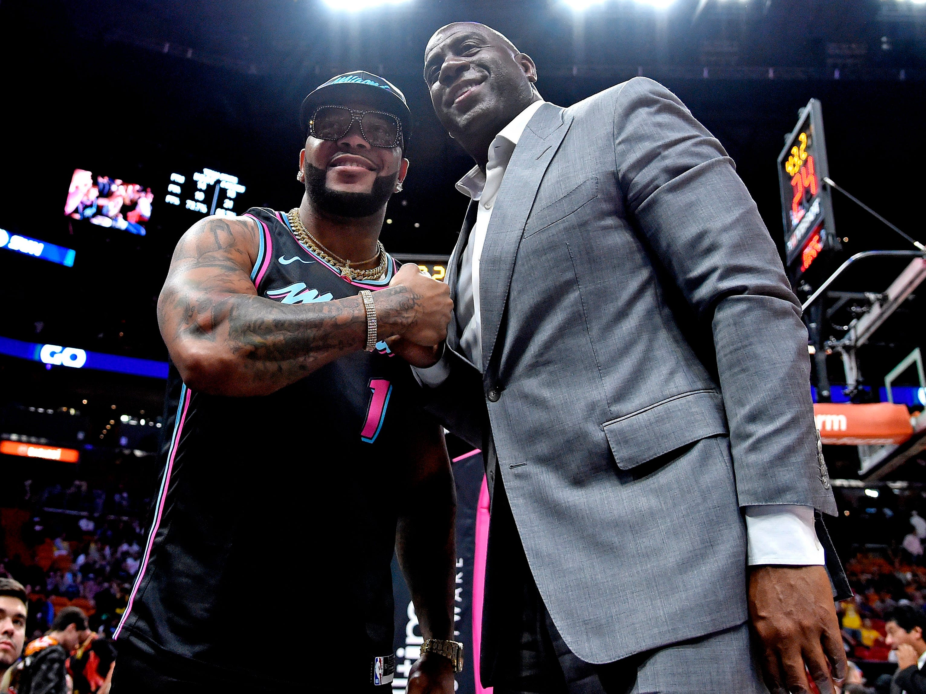 Nov. 18: Lakers executive Magic Johnson, right, and rapper Flo Rida take in the Heat-Lakers game in Miami.