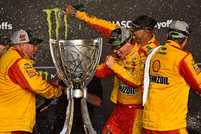 Joey Logano and his team celebrate winning the NASCAR Cup Series championship at Homestead-Miami Speedway.