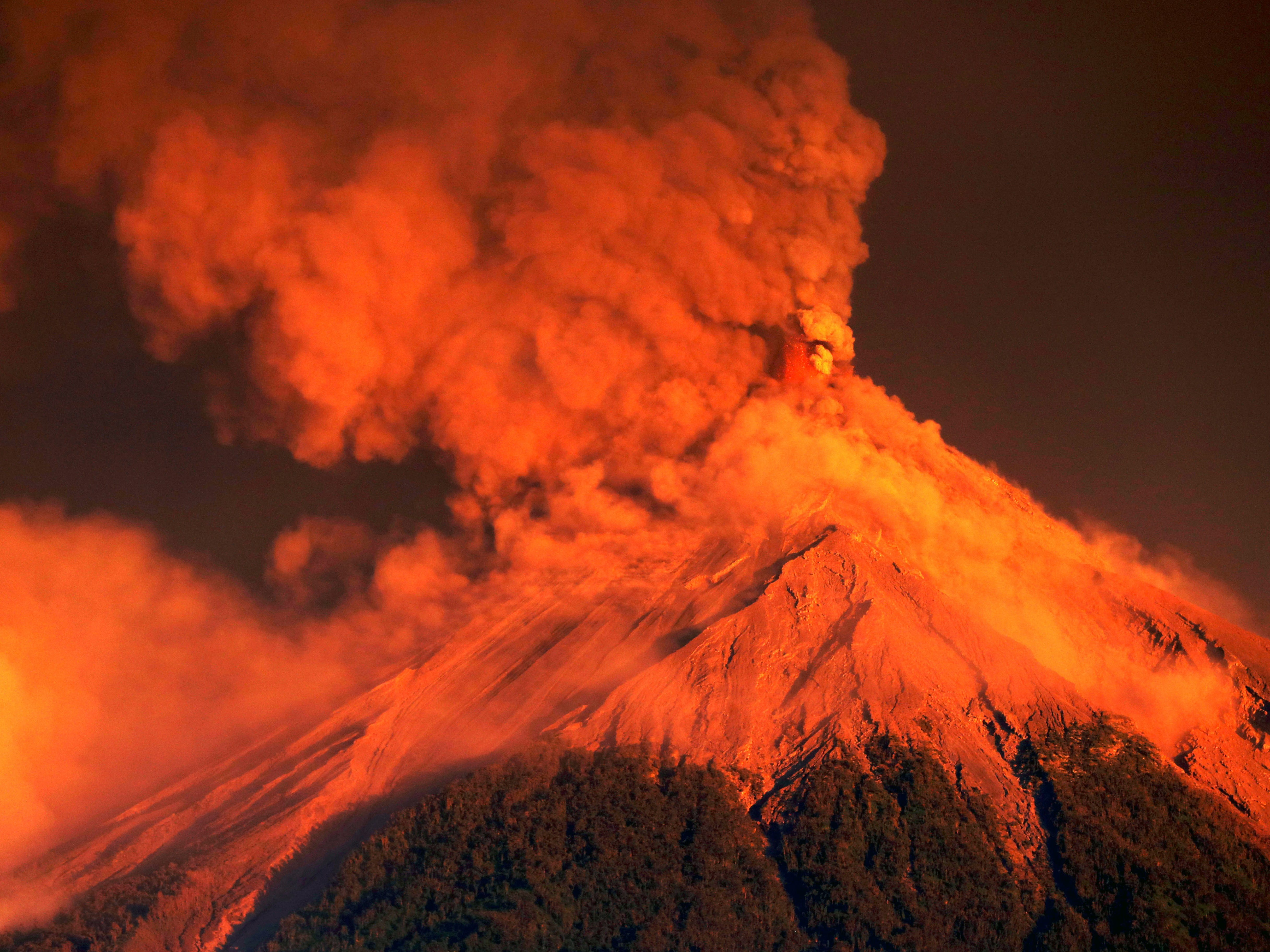 The Fuego volcano erupts at sunrise, Nov. 19, 2018, in Escuintla, Guatemala. Disaster coordination authorities have asked several communities in Guatemala to evacuate and go to safe areas after an increased eruption of the Volcano of Fire.