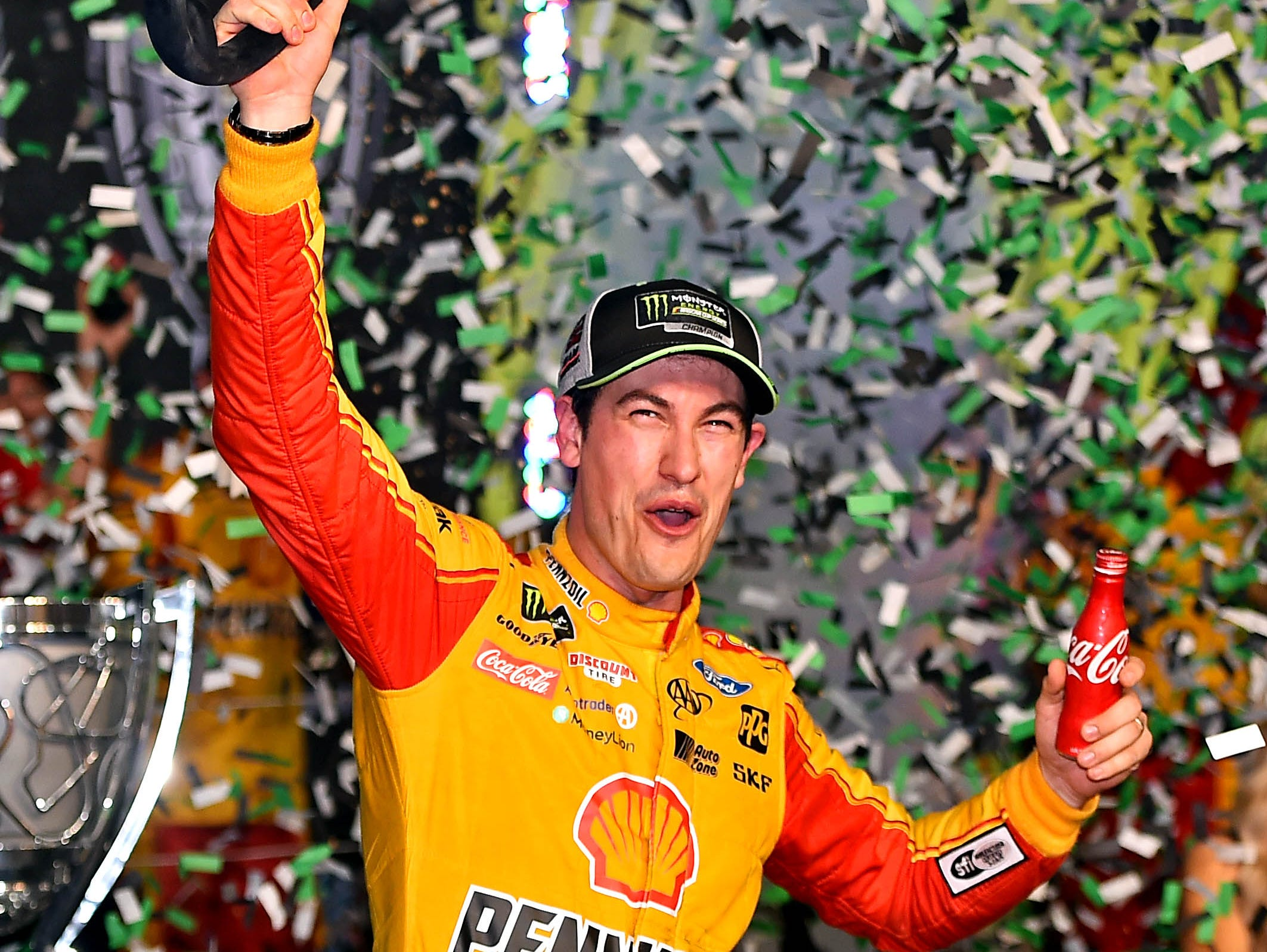 Joey Logano poses for photos after winning the NASCAR Cup championship at Homestead-Miami Speedway.