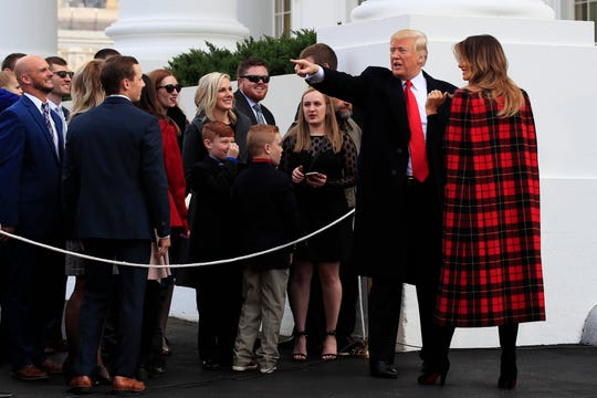 President Trump and first lady Melania Trump wave to invited guests watching as they greeted delivery of the White House Christmas Tree at the North Portico of the White House, Nov. 19, 2018.