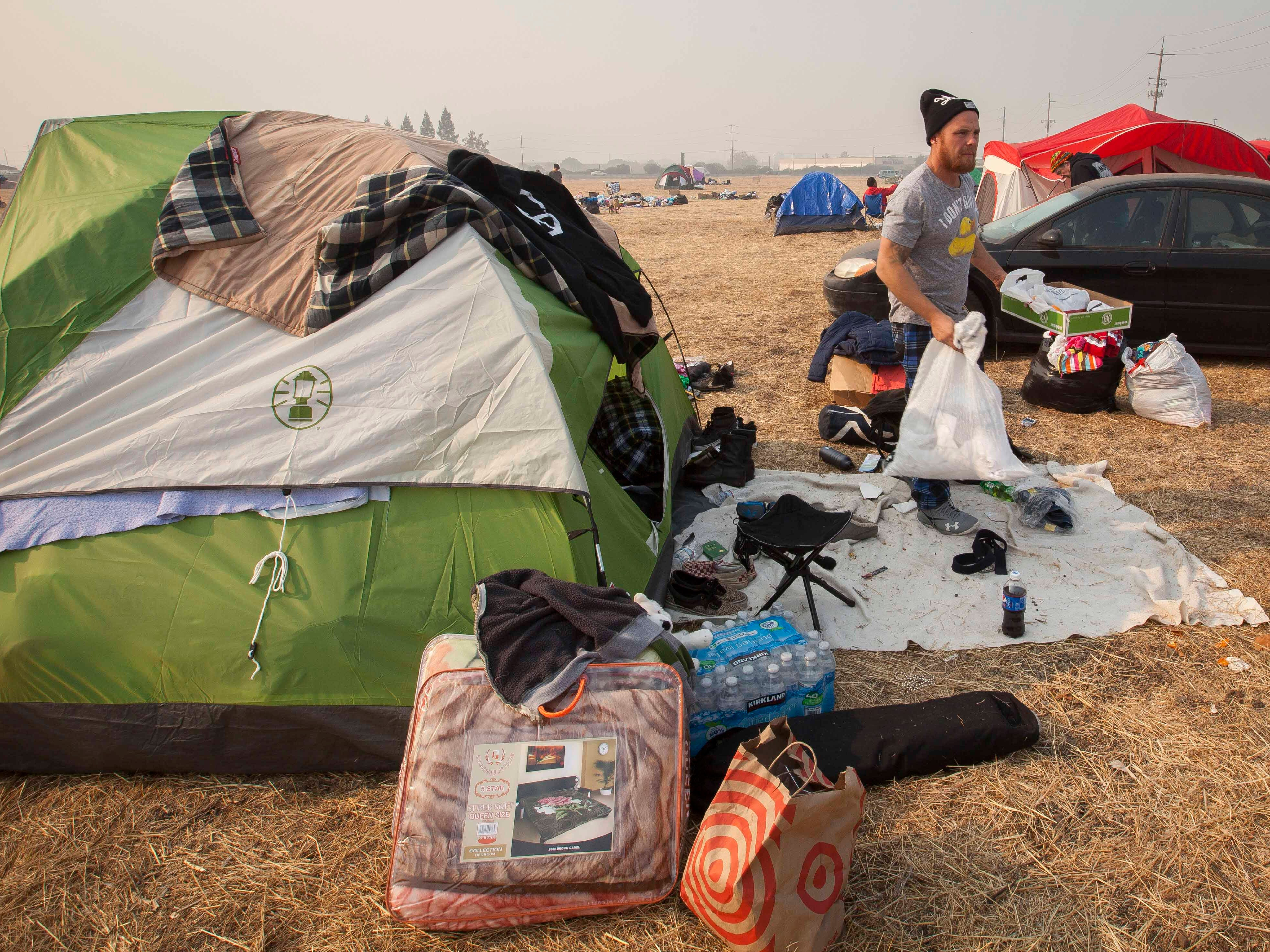 Ryan Vaughn begins to pack his belongings from the field next to the Walmart in Chico, Calif. on Nov. 18, 2018.