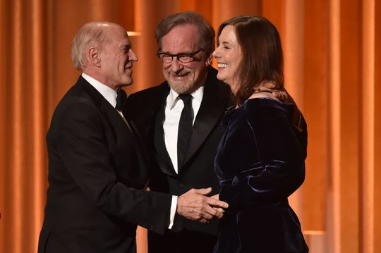 Steven Spielberg (center) embraces producers Kathleen Kennedy (right) and producer Frank Marshall as they accept the Irving G. Thalberg Memorial Award at the Governors Awards.