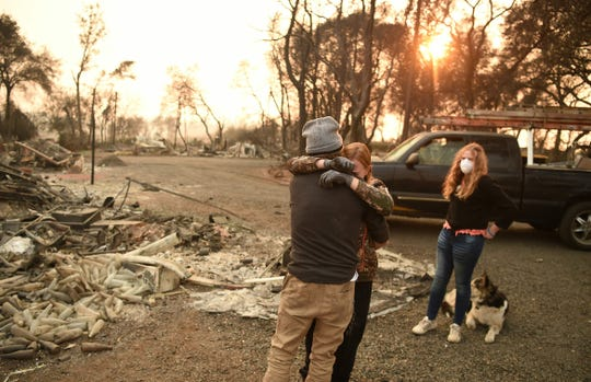 Kimberly Spainhower hugs her husband Ryan Spainhower, with their daughter Chloe Spainhower, 13, right, at the burned remains of their home in Paradise, Calif. on Nov. 18, 2018.