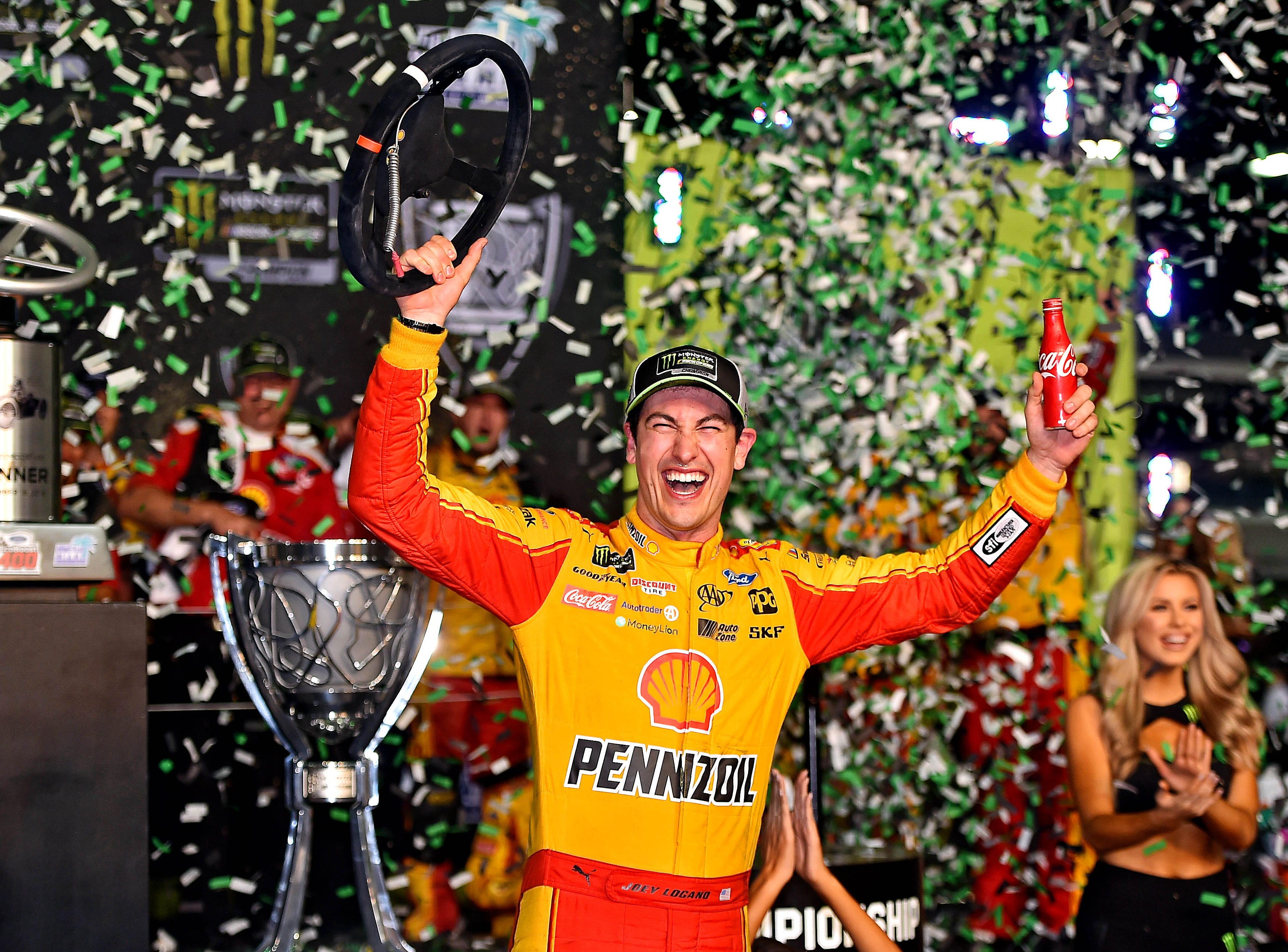 Joey Logano poses for photos after winning the NASCAR Cup Series championship at Homestead-Miami Speedway.