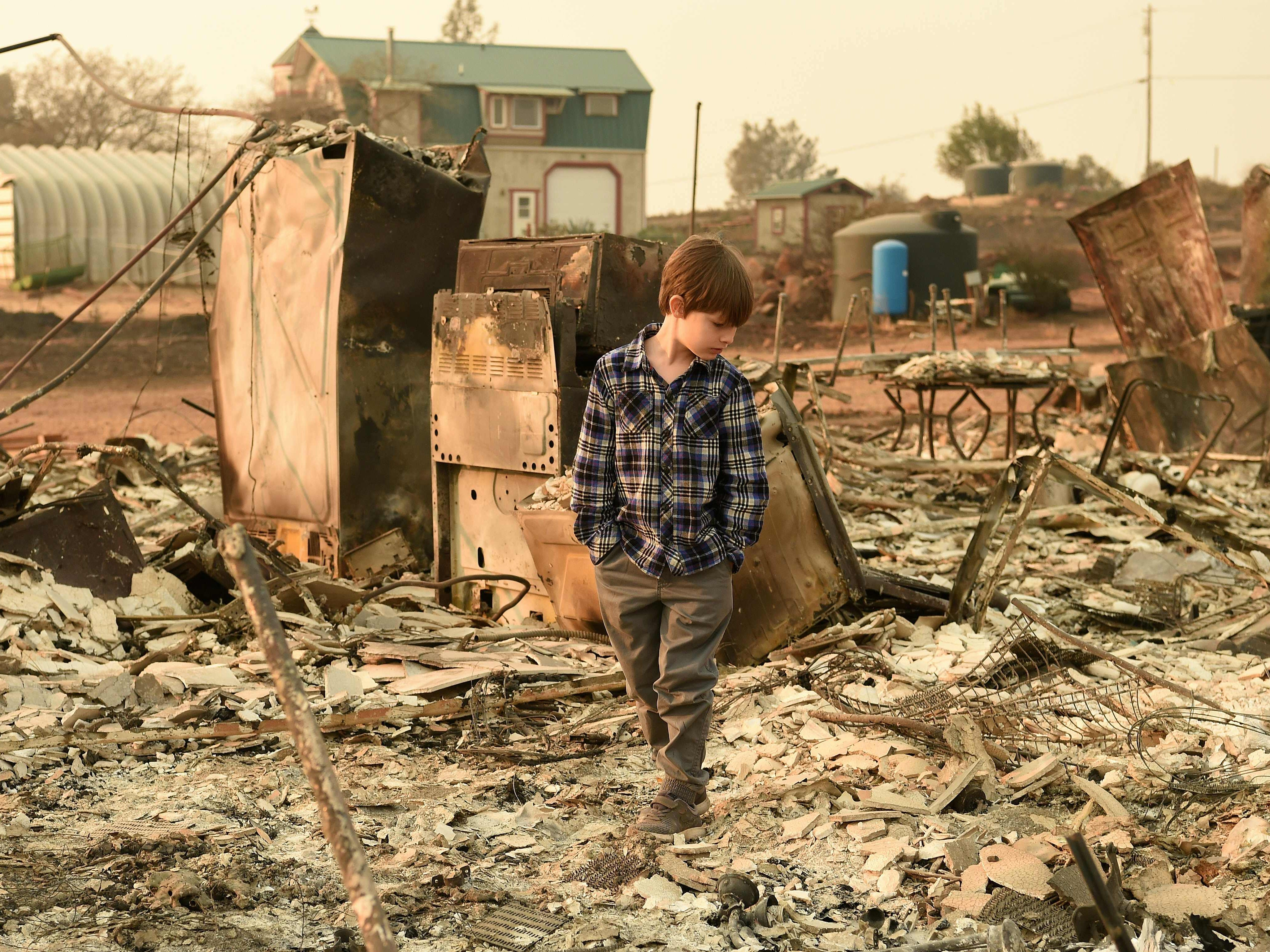 Jacob Saylors, 11, walks through the burned remains of his home in Paradise, Calif. on Nov. 18, 2018. The family lost a home in the same spot to a fire 10 years earlier.