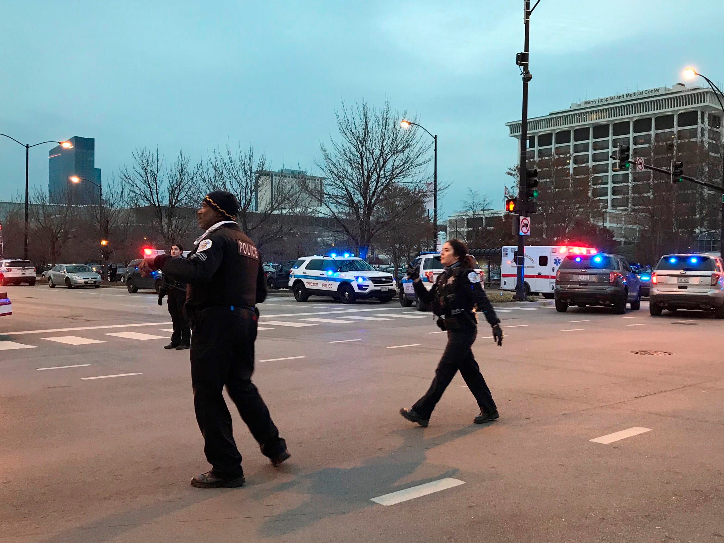 Chicago Police officers work outside Mercy Hospital where authorities say a shooting has wounded multiple people, including a suspect and a police officer on Nov. 19, 2018, in Chicago.