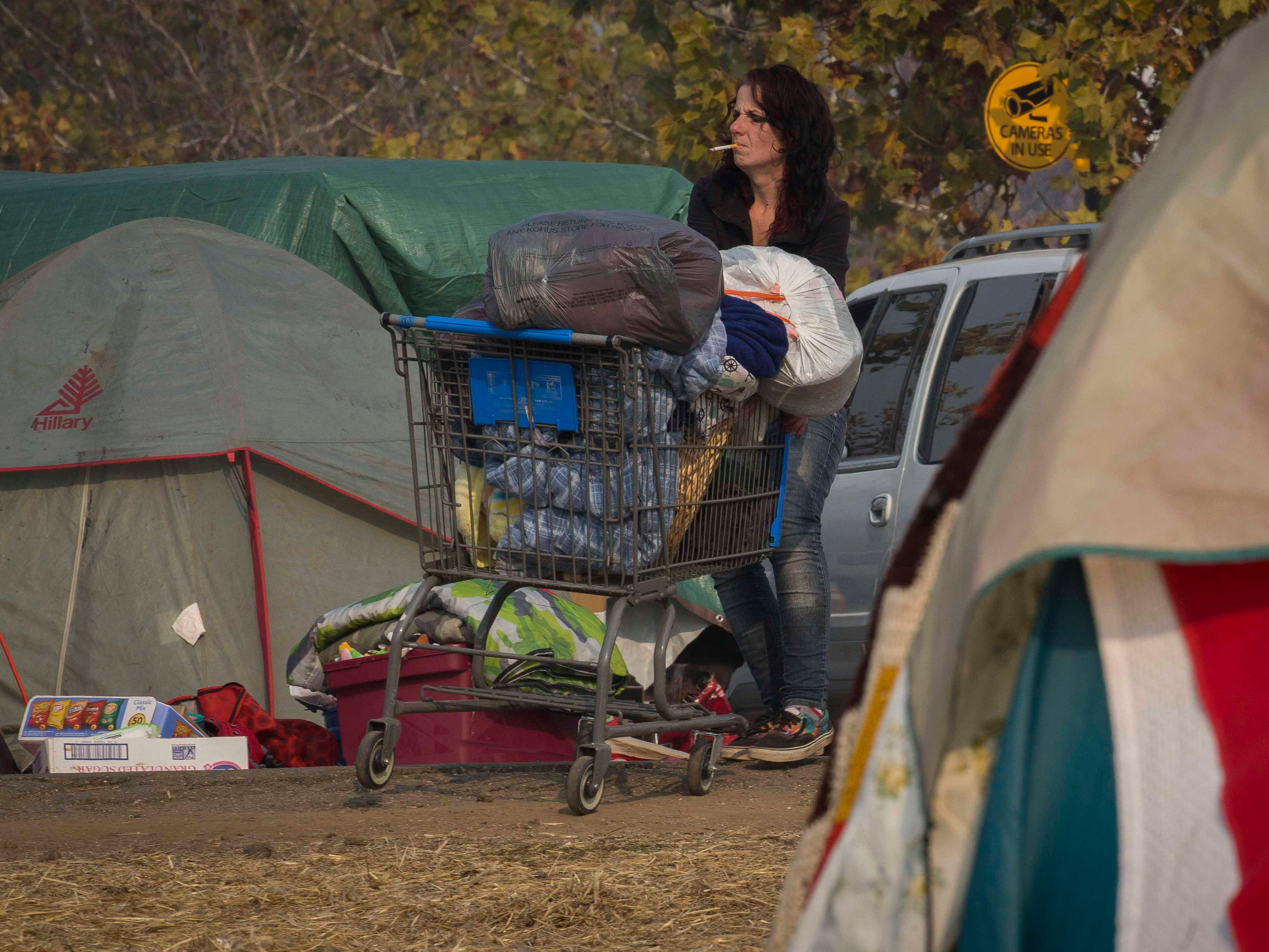 A woman uses a shopping cart to help move her belongings from a field next to the Walmart in Chico, Calif. on Nov. 18, 2018.
