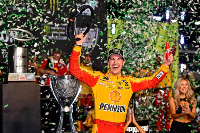 Joey Logano celebrates after winning the Ford EcoBoost 400 and the NASCAR Cup Championship at Homestead-Miami Speedway.