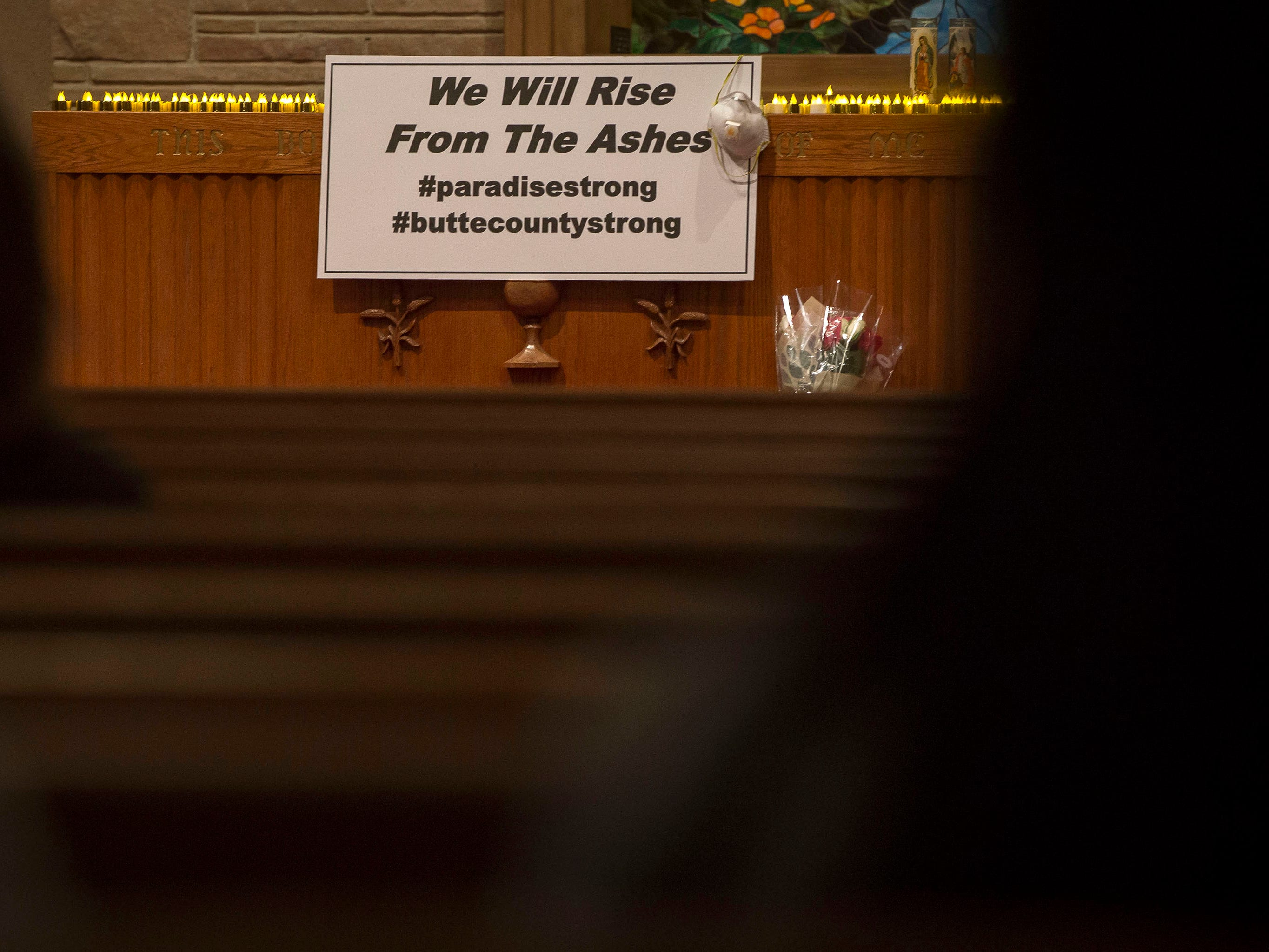A sign is displayed during a candlelight vigil and service at the First Christian Church of Chico, Sunday, Nov. 18, 2018, in Chico, Calif.