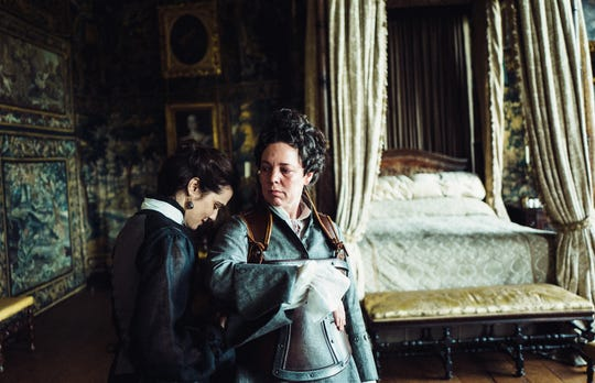"Lady Sarah (Rachel Weisz, left) attends to the whims of Queen Anne (Olivia Colman) in ""The Favourite."""
