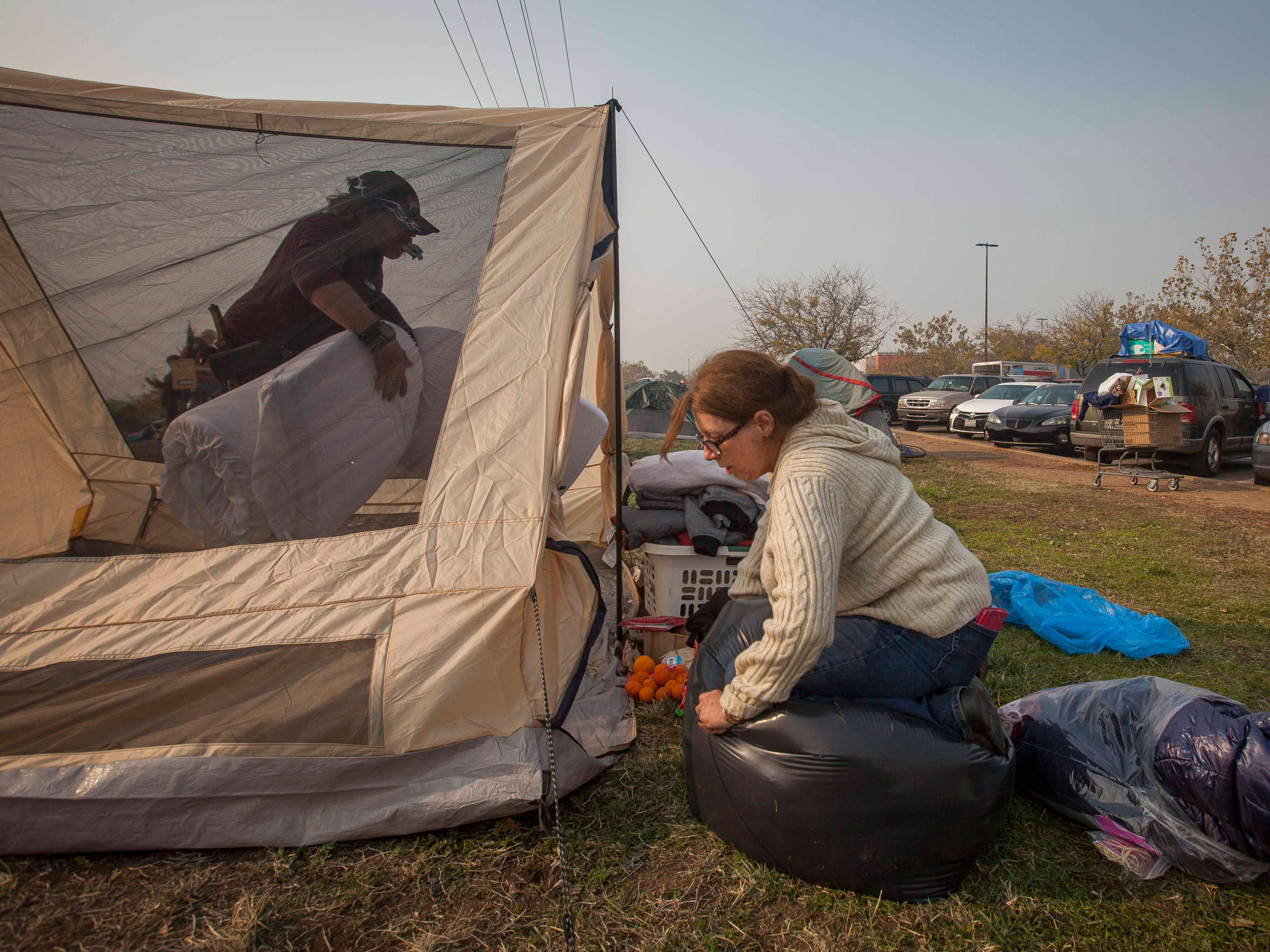 Cindy De Lano and her boyfriend John Richards work to pack up their belongings from the field next to a Walmart in Chico, Calif. on Nov. 18, 2018.