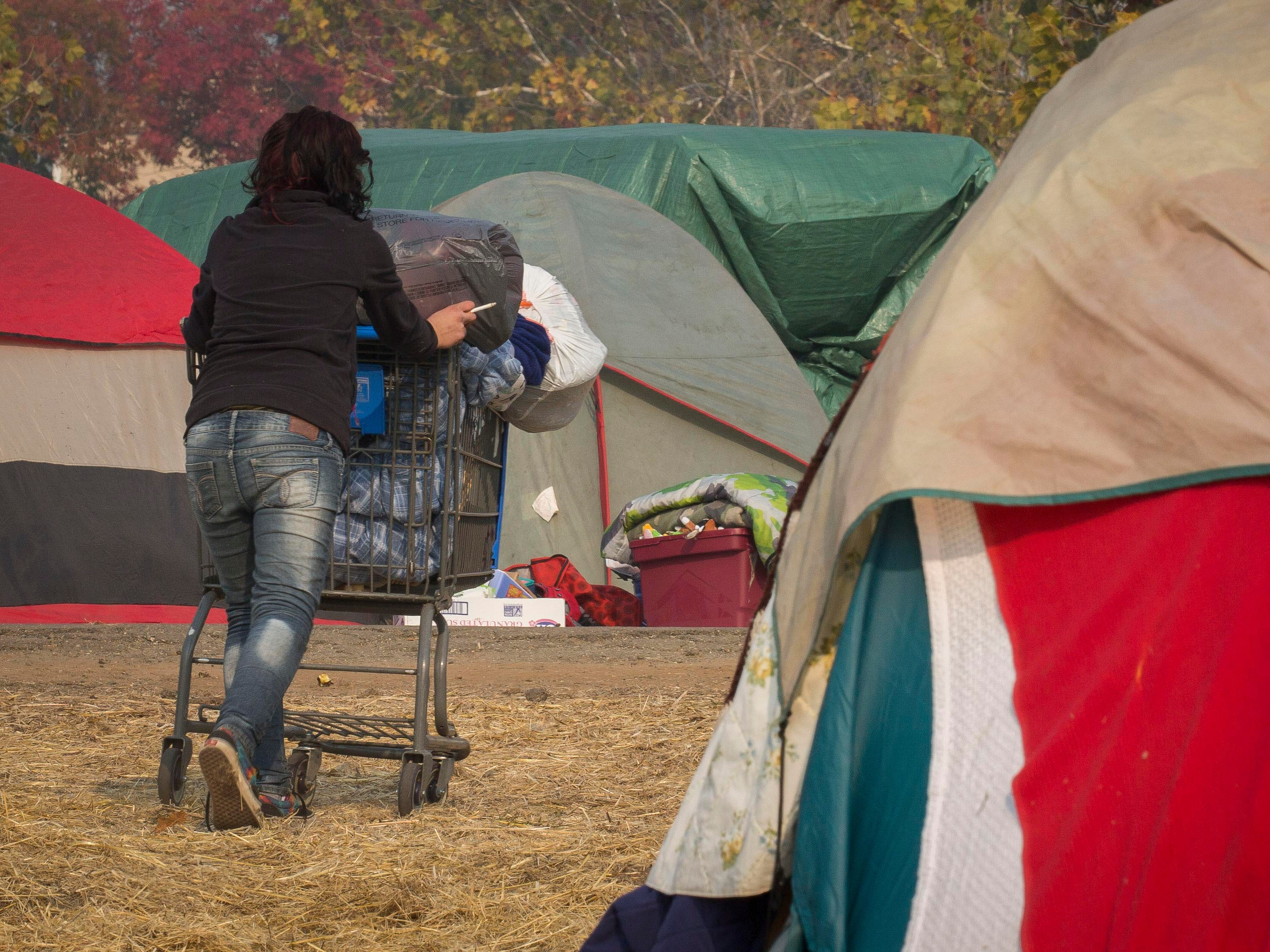 A woman uses a shopping cart to help move her belongings from the field next to the Walmart in Chico, Calif., on Nov. 18, 2018, as officials work to close the make-shift camp that formed as people fled the Camp Fire. FEMA, Red Cross and other agencies were helping to place the remaining people at the camp.