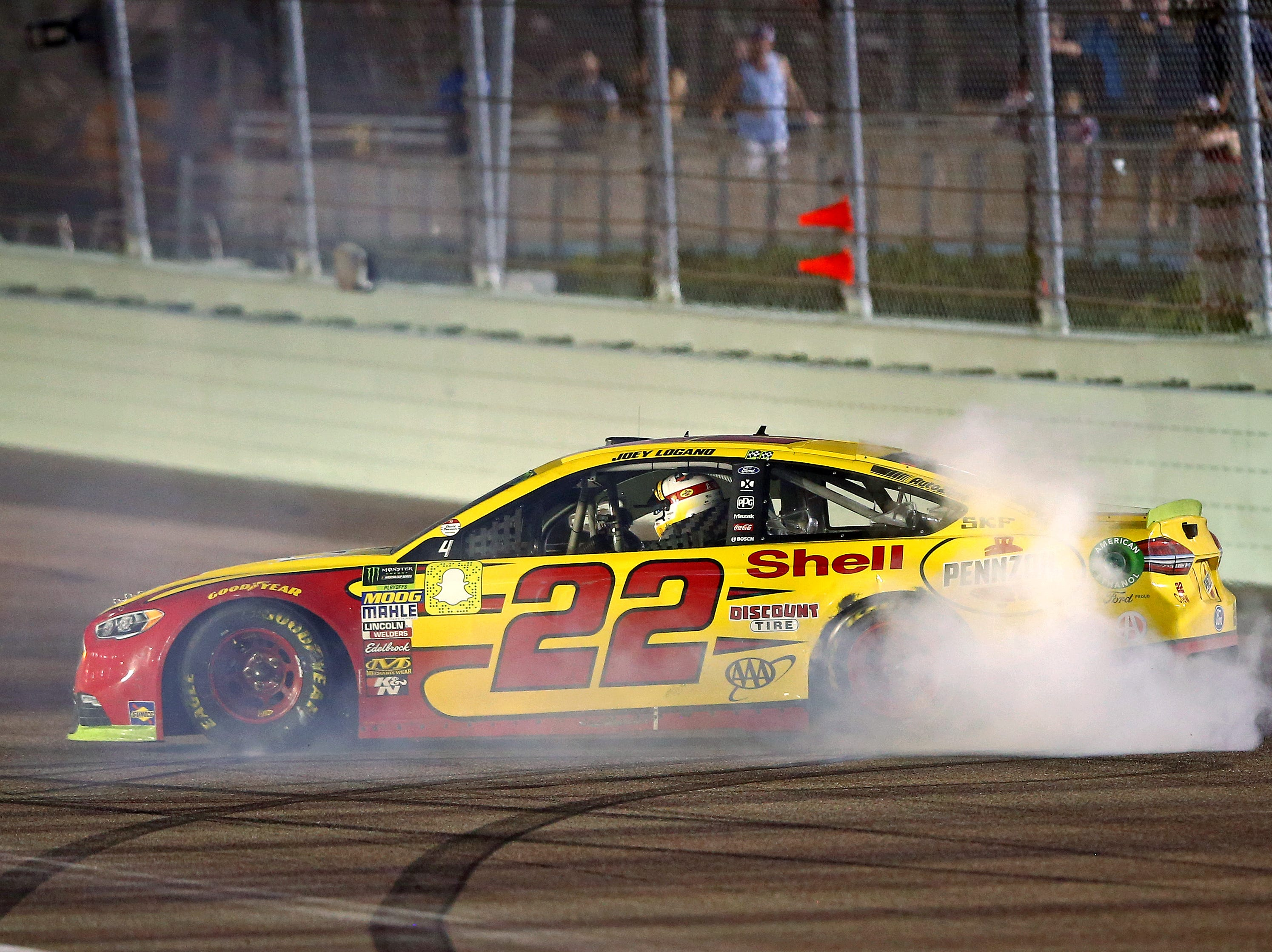 Joey Logano (22) celebrates winning the Ford EcoBoost 400 and the NASCAR Cup Series championship at Homestead-Miami Speedway.