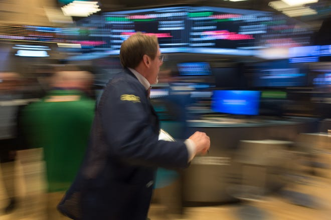 A trader runs across the floor after the Dow Jones closing bell at the New York Stock Exchange, February 21, 2017 in New York. 