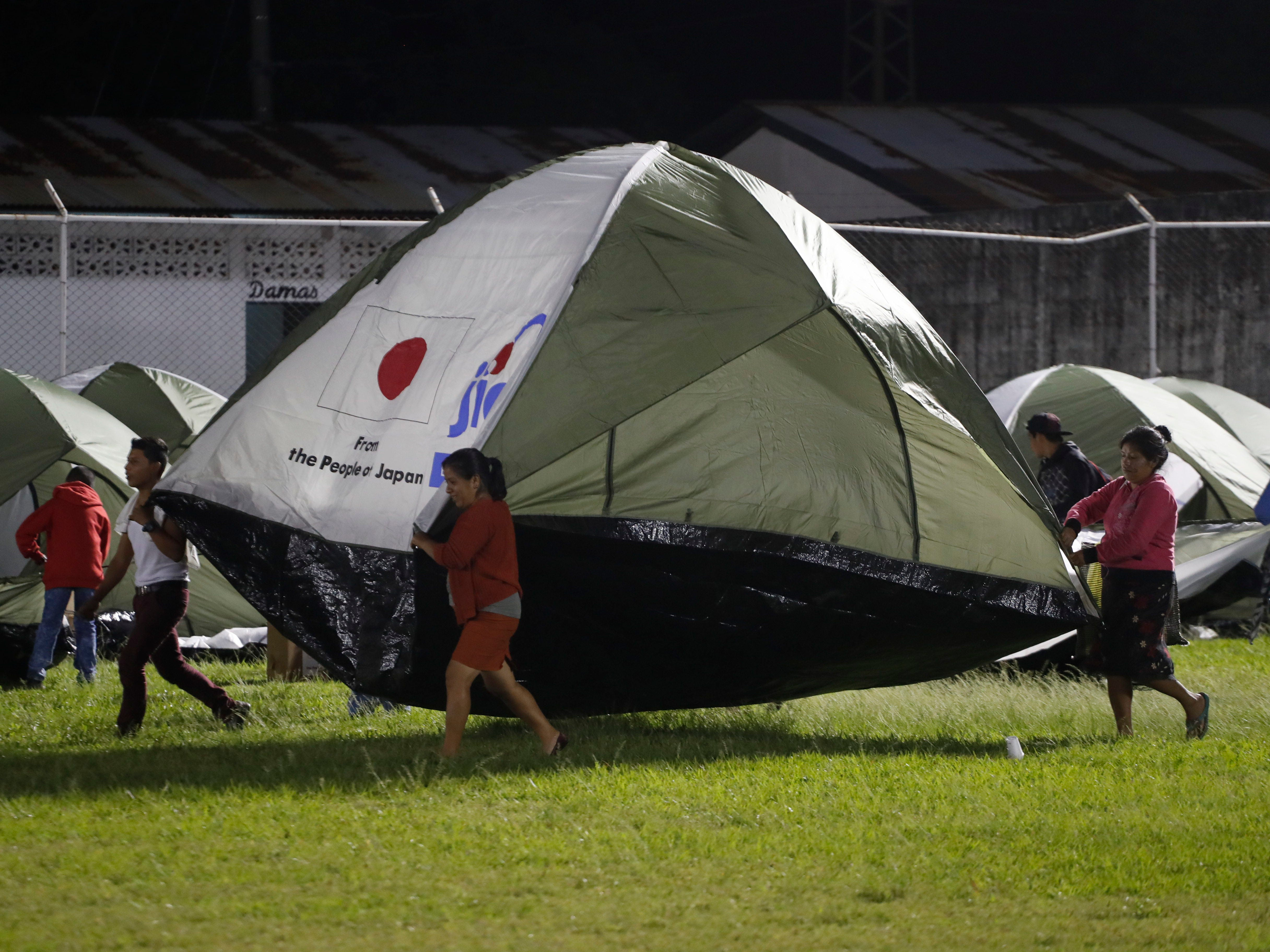 Evacuees from the Volcano of Fire area carry a tent at an emergency shelter in Escuintla, Guatemala, Monday, Nov. 19, 2018.