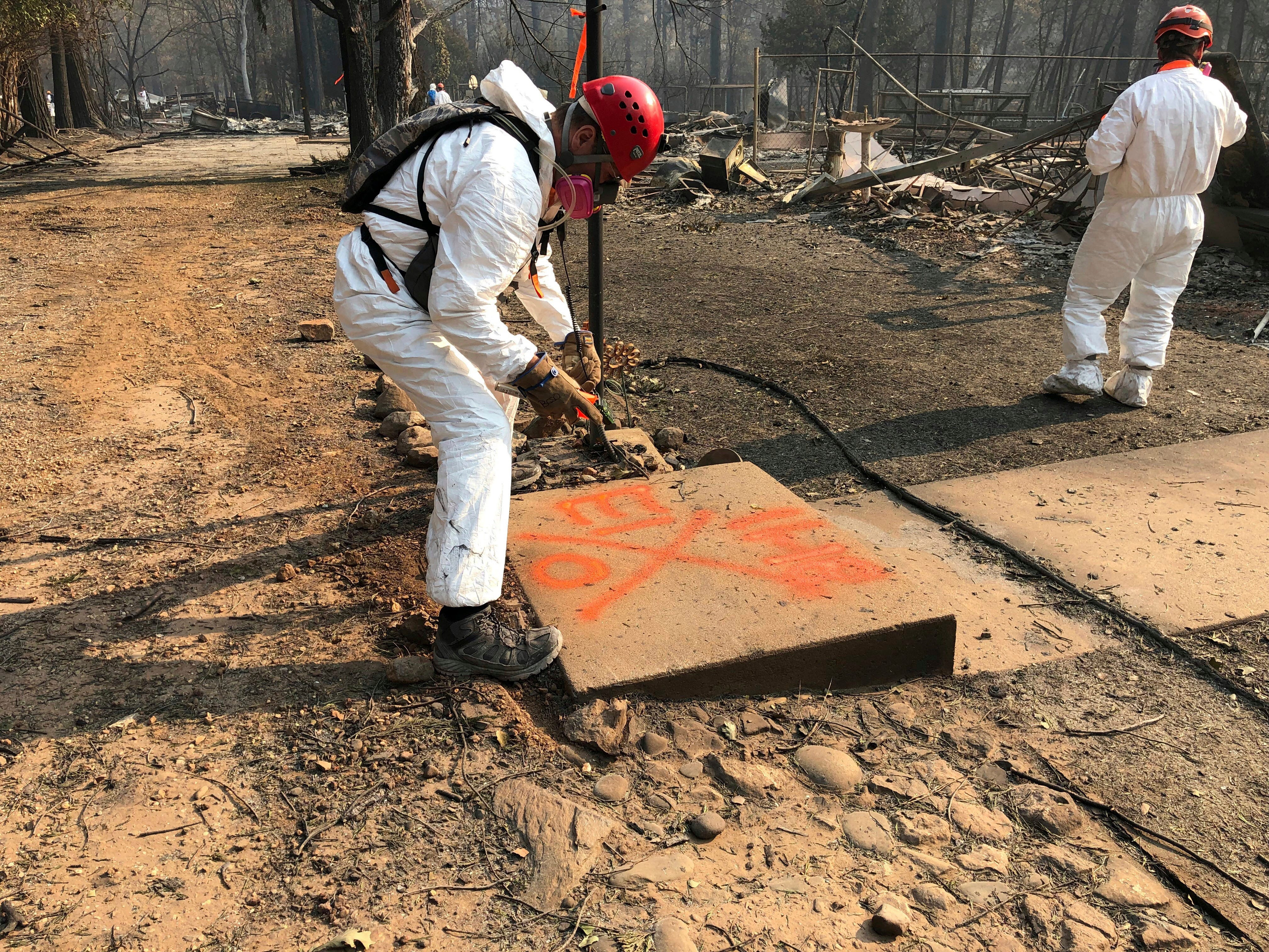 A volunteer member of an El Dorado County search and rescue team uses orange spray paint to mark the ruins of a home to show that no human remains were found at the location in Paradise, Calif. on  Nov. 18, 2018.