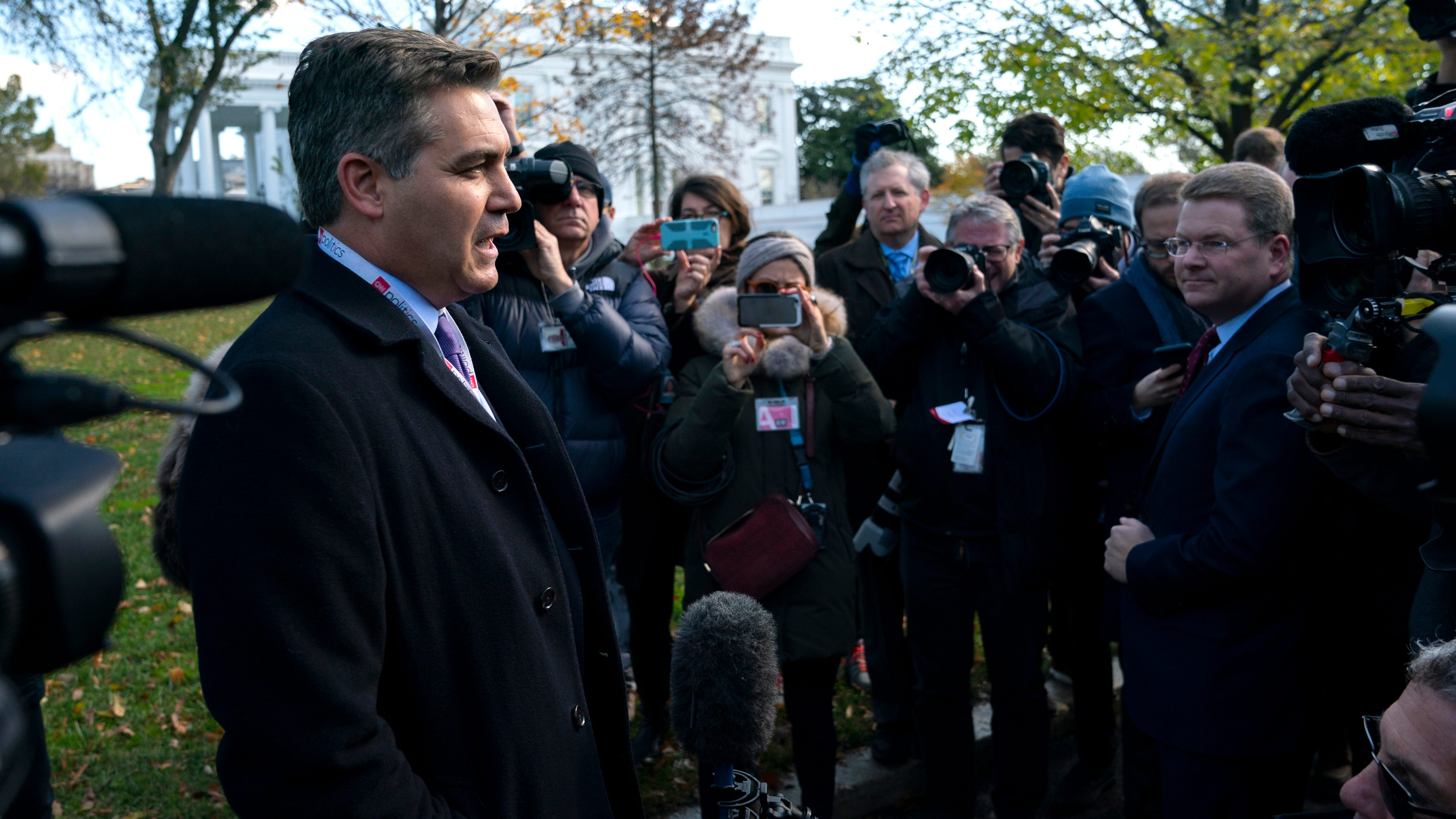 CNN journalist Jim Acosta talks with reporters as he arrives at the White House after having his press pass restored, Nov. 16, 2018, in Washington.
