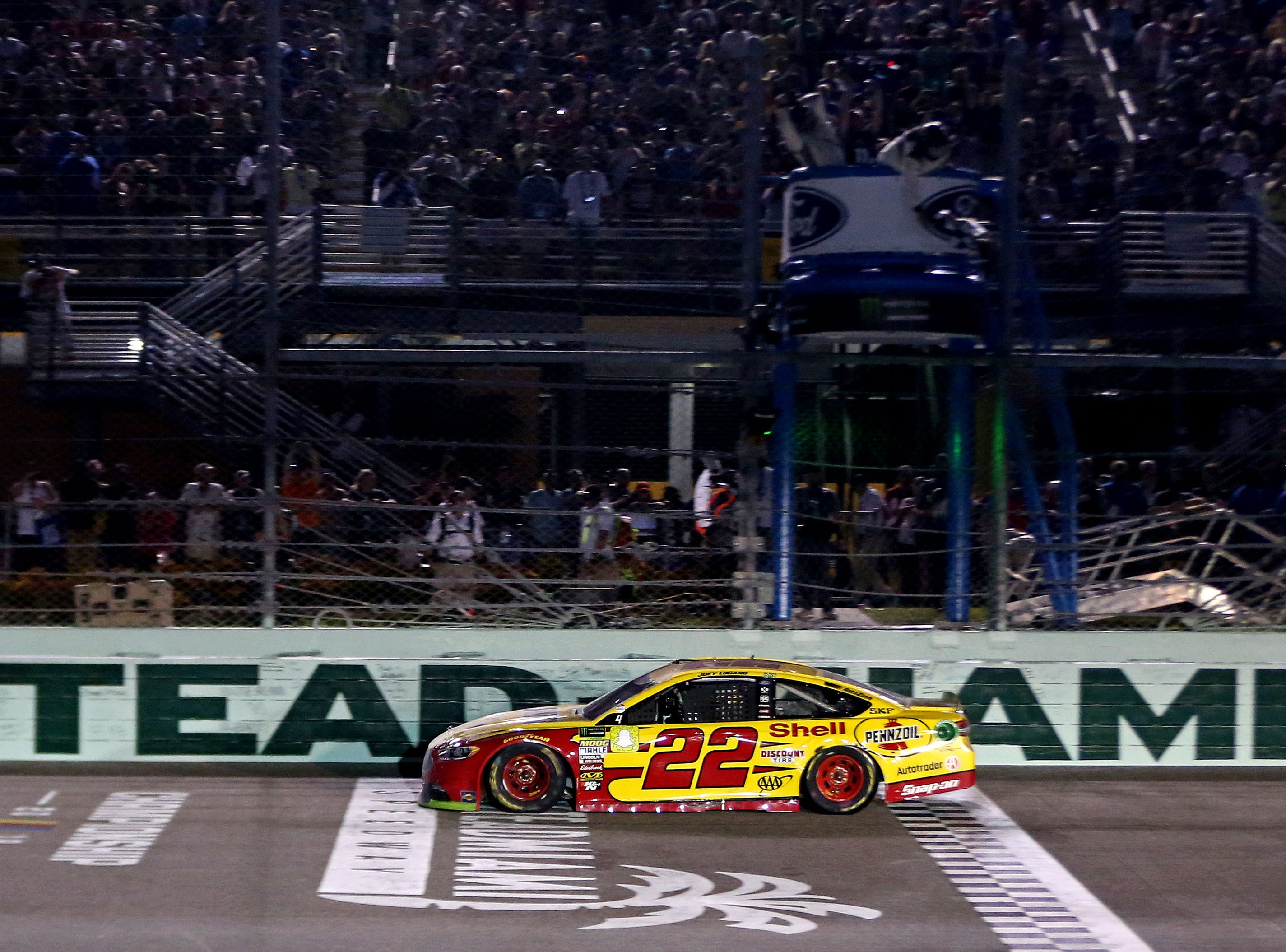 Joey Logano (22) crosses the finish line to win the Ford EcoBoost 400 and the NASCAR Cup Series Championship at Homestead-Miami Speedway.