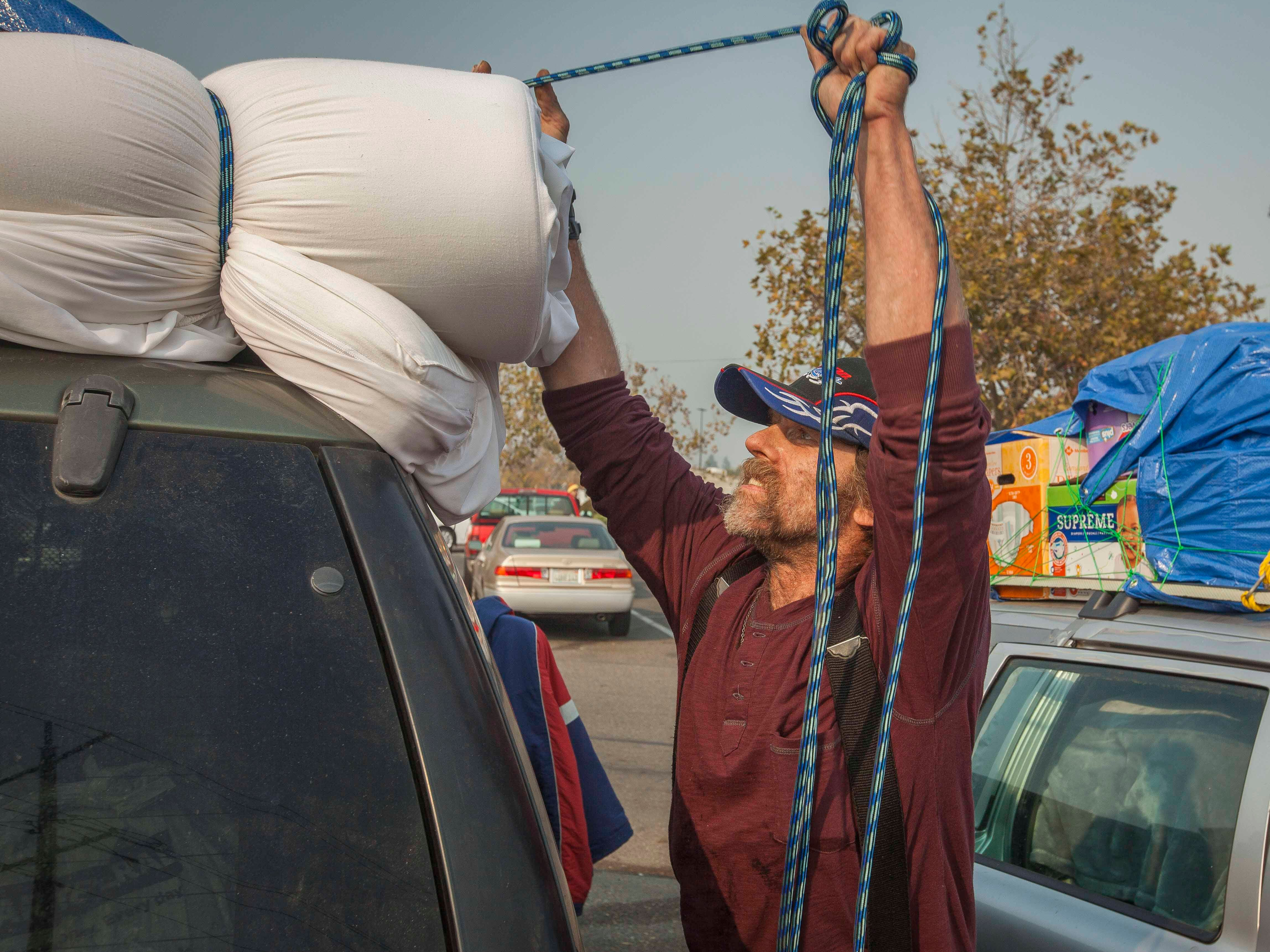 John Richards secures items on top of his SUV as he and his girlfriend pack up their belongings from the field next to the Walmart in Chico, Calif. on Nov. 18, 2018.