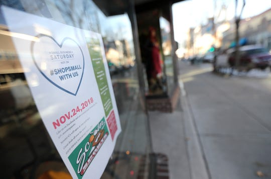 A sign promoting Small Business Saturday hangs in the window of Scooter G Sports in downtown Appleton.