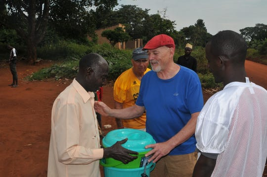 The Rev. Terry Chapman (in blue) giving a water filtration lesson to a village chief in Uganda.