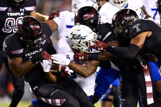 Tulsa Golden Hurricane running back Shamari Brooks (center) is tackled by Temple Owls linebacker Chapelle Russell (far left) and linebacker Sam Franklin (second from right) and  linebacker Shaun Bradley (right) in September.