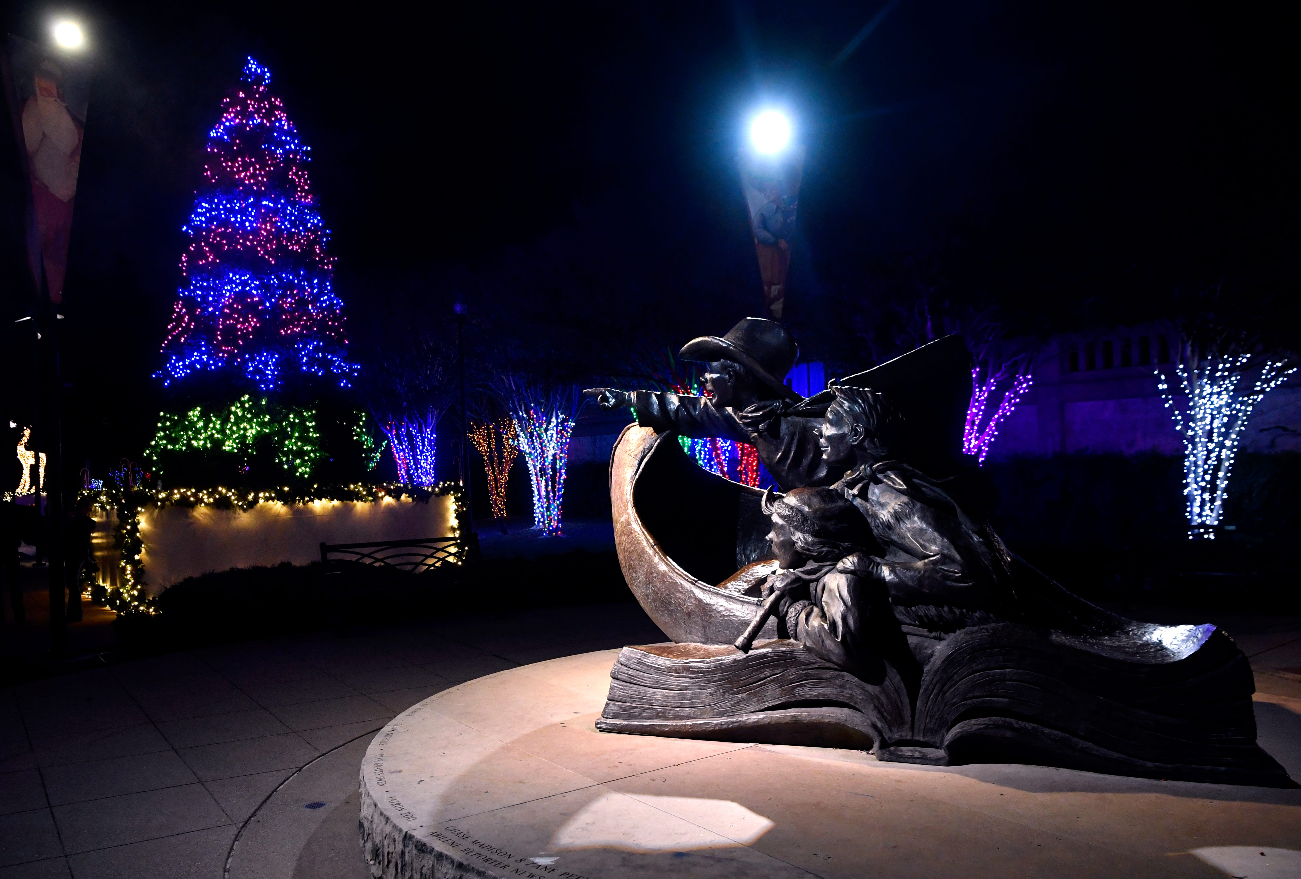 """The statue """"Childhood's Great Adventure"""" seems to point at a Christmas tree made of lights in Everman Park last fall."""