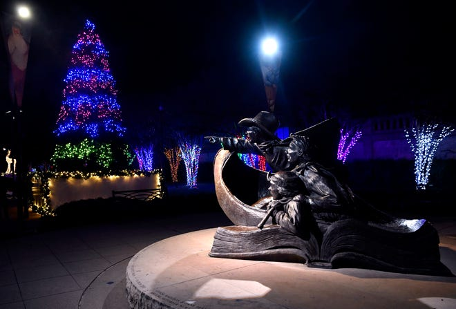 "The statue ""Childhood's Great Adventure"" seems to point at a Christmas tree made of lights in Everman Park. The lights will officially be turned on Monday."