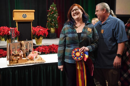 "Julie and Michael Andreacola, of Indian Trail, stand next to their grand prize entry ""Gearing up for Christmas,"" at the Omni Grove Park Inn's annual gingerbread competition Nov. 19, 2018."
