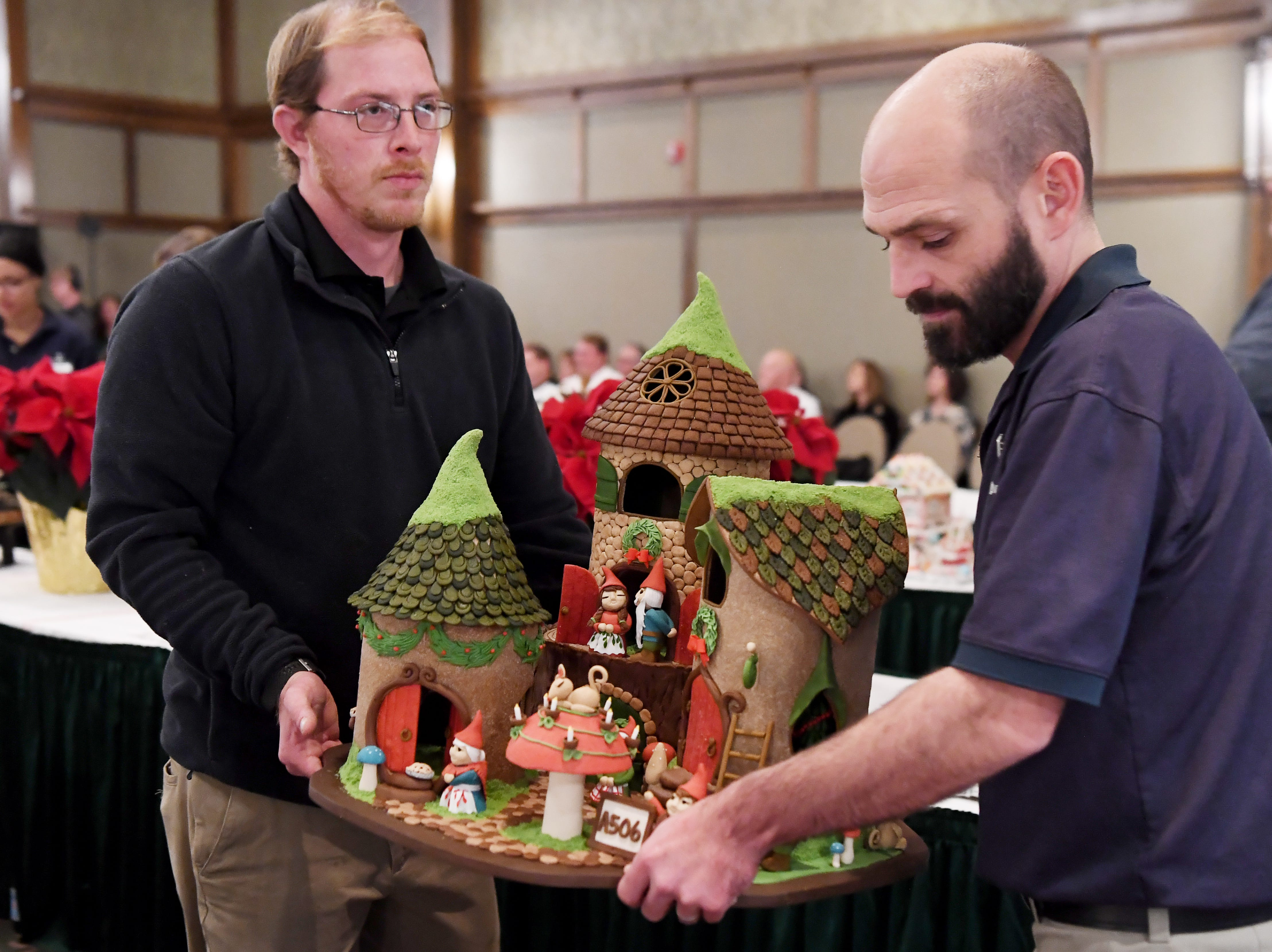 """Rebecca Grizzle's entry, """"Home sweet Gnome,"""" is carried to the finalists table during the Omni Grove Park Inn's National Gingerbread House Competition Nov. 19, 2018."""