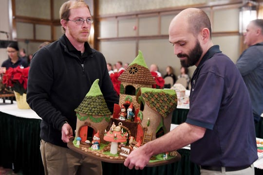 """Rebecca Grizzle's entry, """"Home Sweet Gnome,"""" is carried to the finalists table during the Omni Grove Park Inn's National Gingerbread House Competition on Nov. 19, 2018."""