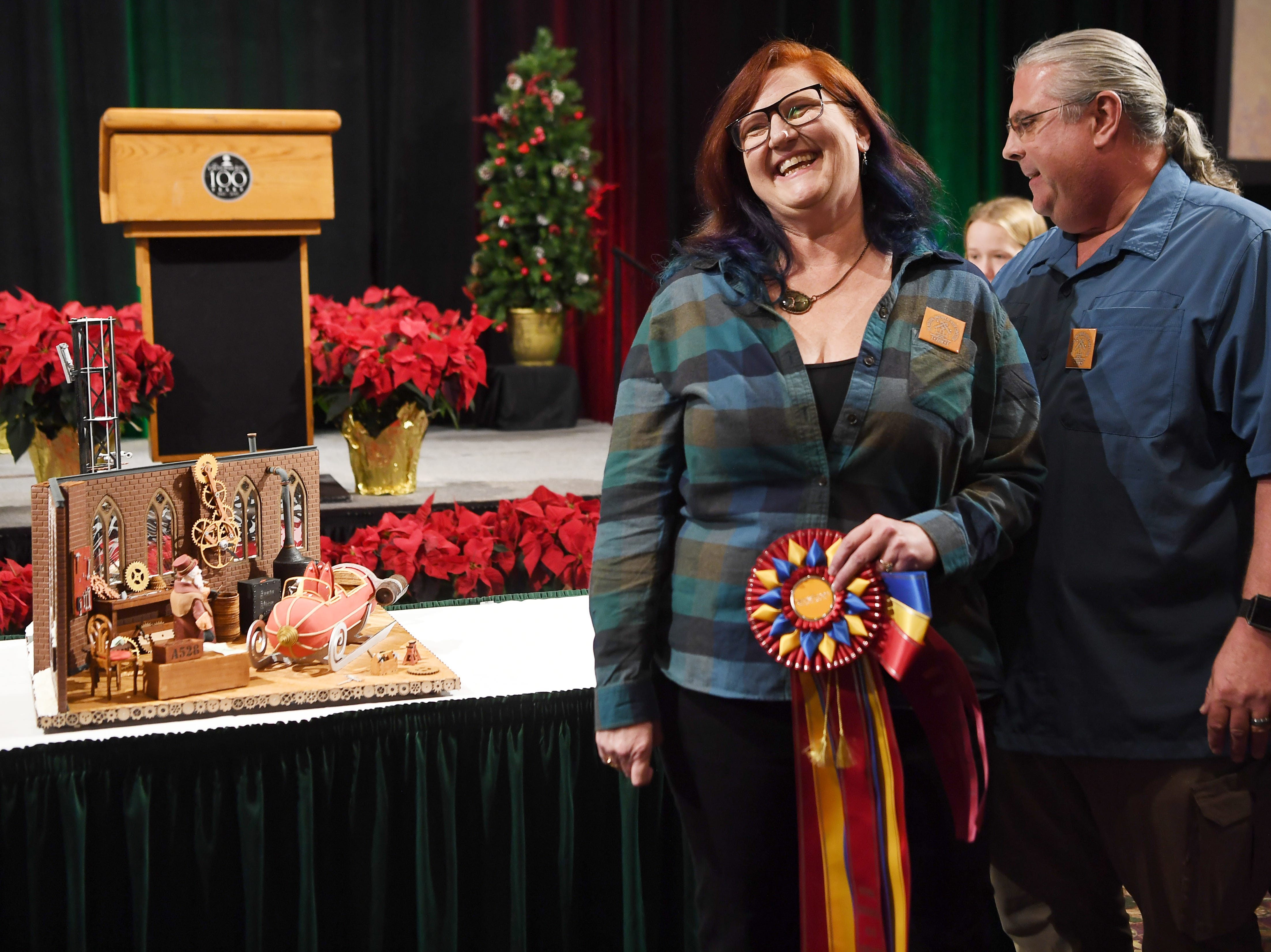 """Julie and Michael Andreacola, of Indian Trail, stand next to their grand prize entry """"Gearing up for Christmas,"""" at the Omni Grove Park Inn's annual gingerbread competition Nov. 19, 2018."""