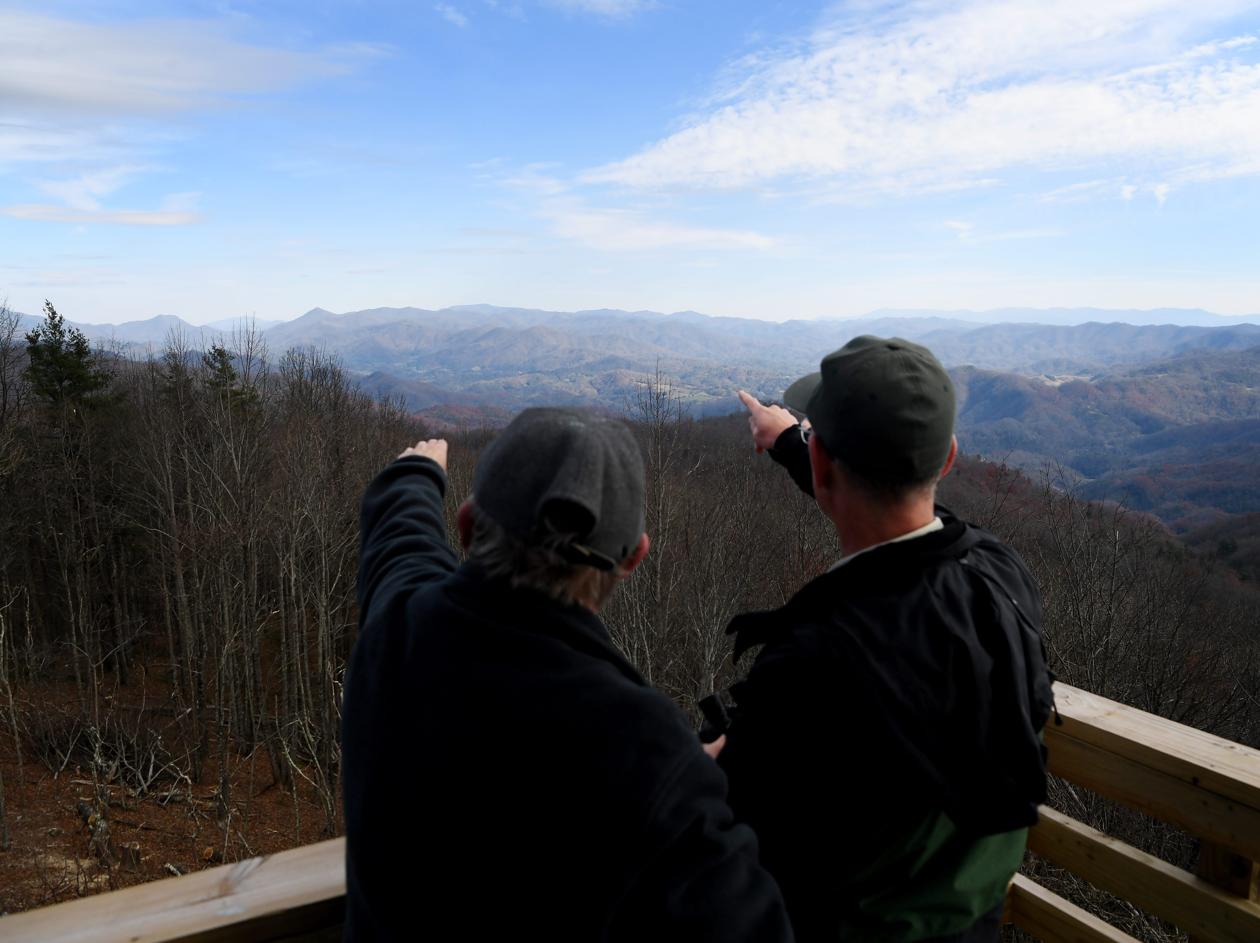 Rob Kelly, left, of Hot Springs, spots mountain peaks along the horizon with Richard Thornburgh, Appalachian District Ranger with the US Forest Service, atop the newly restored Rich Mountain lookout tower near Hot Springs Nov. 19, 2018.