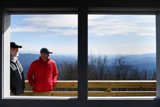 Morgan Sommerville, the southern regional director of the Appalachian Trail Conservancy, and Peter Barr, coordinator of the North Carolina chapter of the Forest Fire Lookout Association, take in the view atop the newly restored Rich Mountain lookout tower near Hot Springs Nov. 19, 2018.