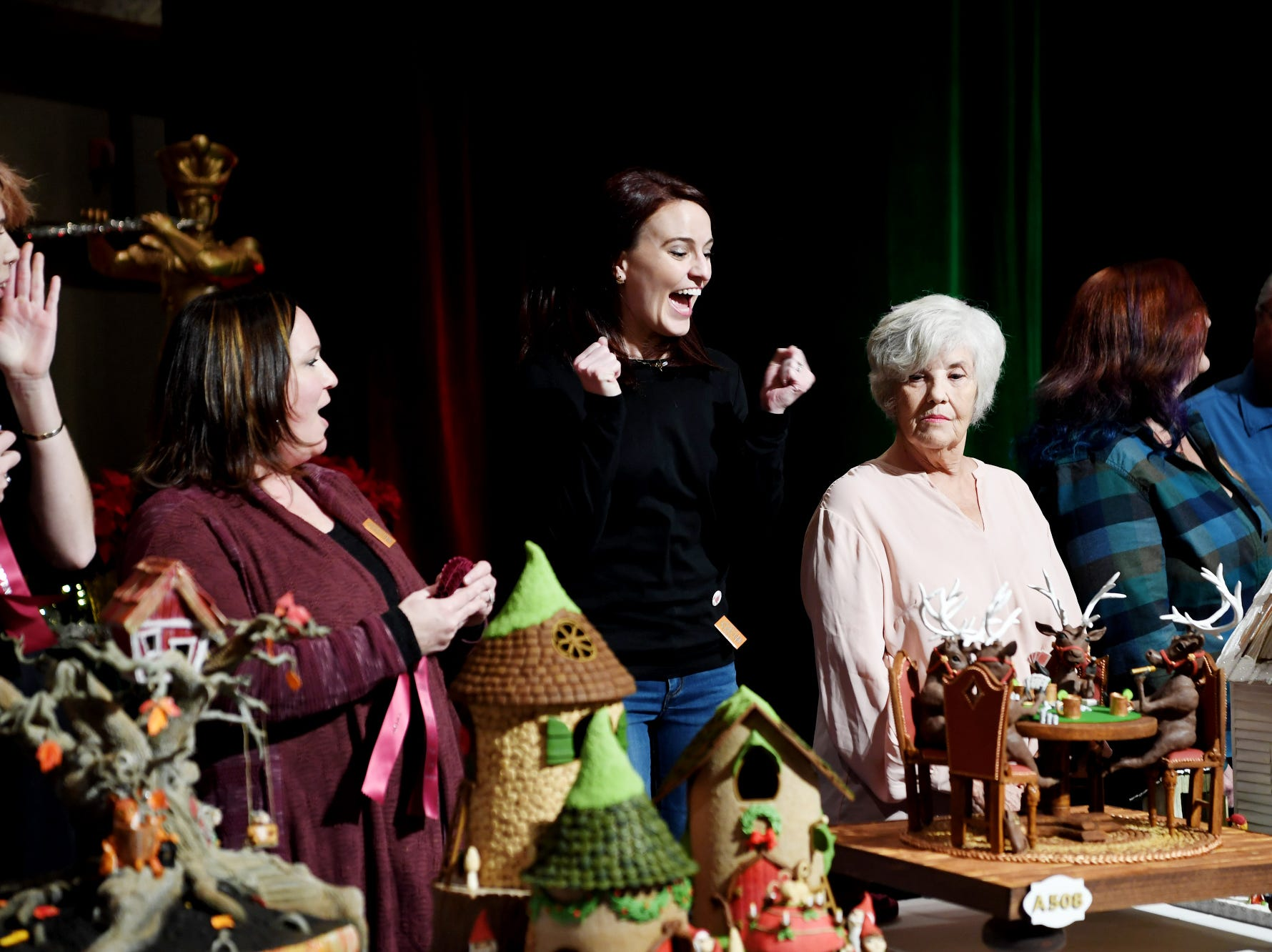 """Grier Rubeling reacts as her entry, """"Reindeer playing Poker,"""" is announced the third-place winner in the Omni Grove Park Inn's annual gingerbread competition Nov. 19, 2018."""