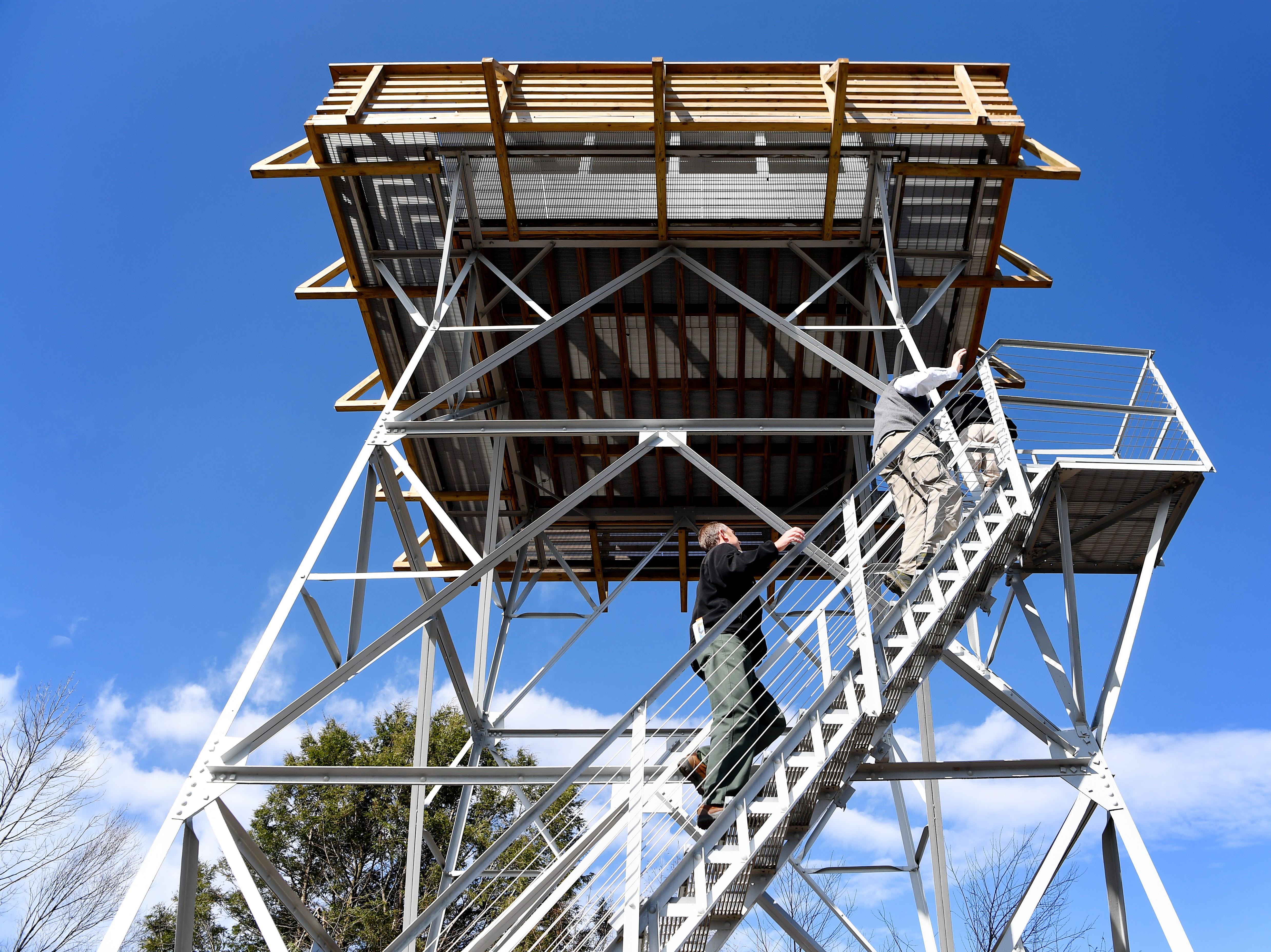 People ascend the stairs to see the view from the Rich Mountain lookout tower near Hot Springs Nov. 19, 2018.