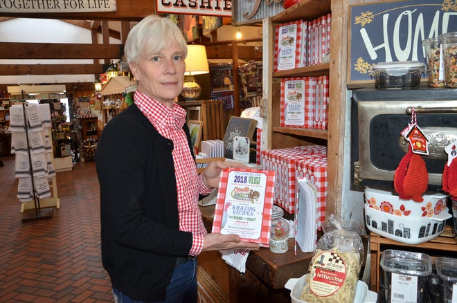 One of the owners of Cornwell's Turkeyville, Patti Cornwell, holds up the cookbook Turkeyville published for its 50th anniversary.