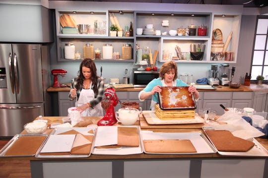 Bonni Phelps stacks cake layers while Monique Chavez stirs icing.