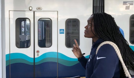 """""""Is this one us?"""" asks Tichina Carmon, who was taking the light rail and ferry back to Kitsap County for the first time."""
