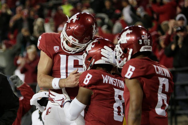 Washington State's Gardner Mishew (16), Easop Winston Jr. (8) and Jamire Calvin (6) celebrate a score during Saturday win over Arizona in Pullman. Minshew leads a Cougars offense that is especially potent, even by the standards of WSU's Air Raid offense.